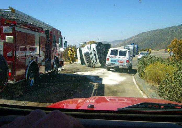Truck overturns blocking 243