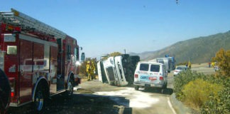 Truck overturns blocking 243